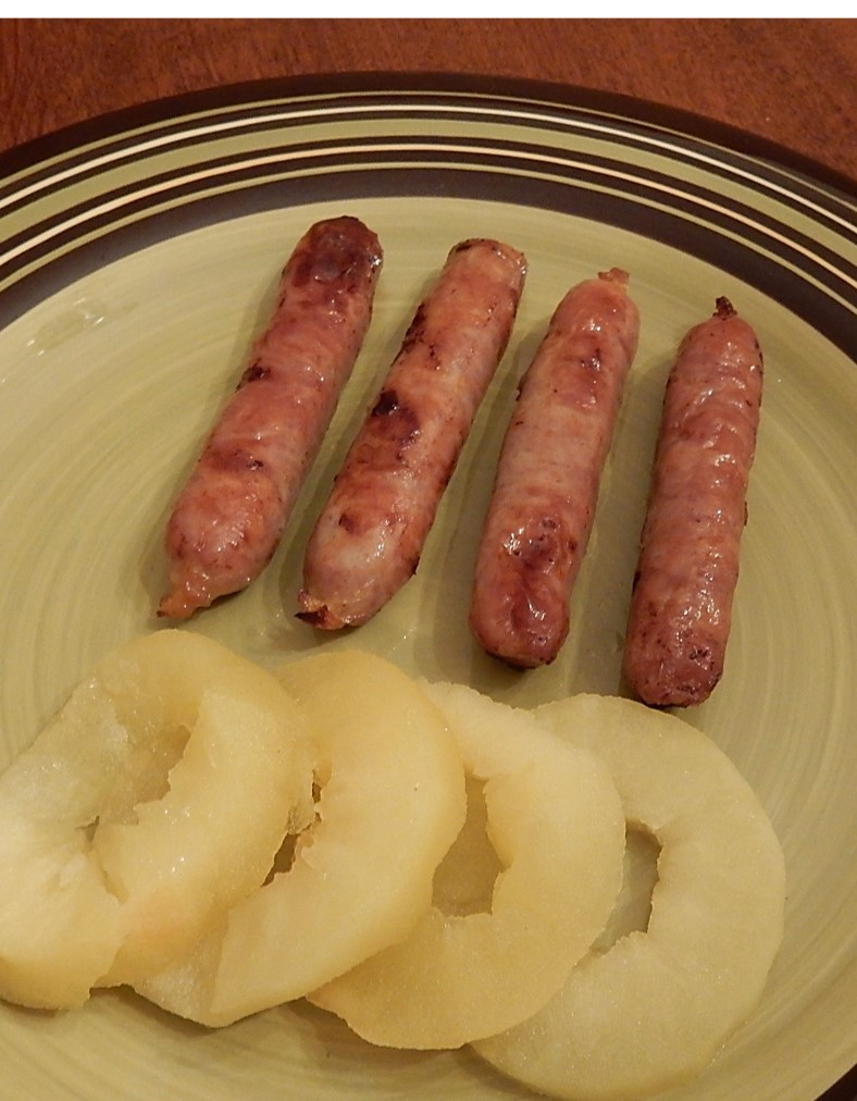 Sausage link and apple rings on plate