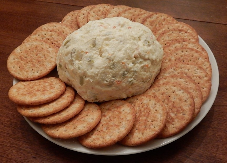 Cheese ball surrounded by crackers on a plate