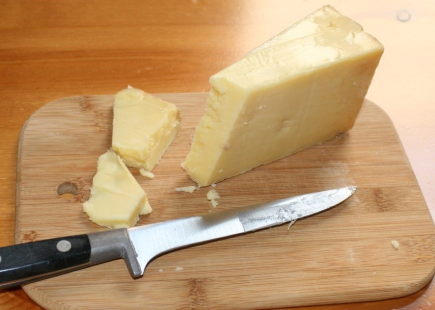 Cheddar Cheese and Knife on Cutting Board