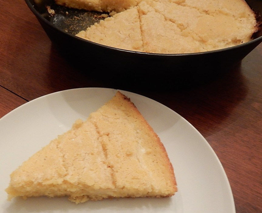 Piece of Spider Cornbread on plate with additional cornbread in background in skillet